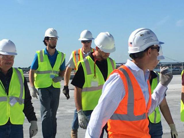 Individuals dressed in hard hats and safety vests walking across a construction area